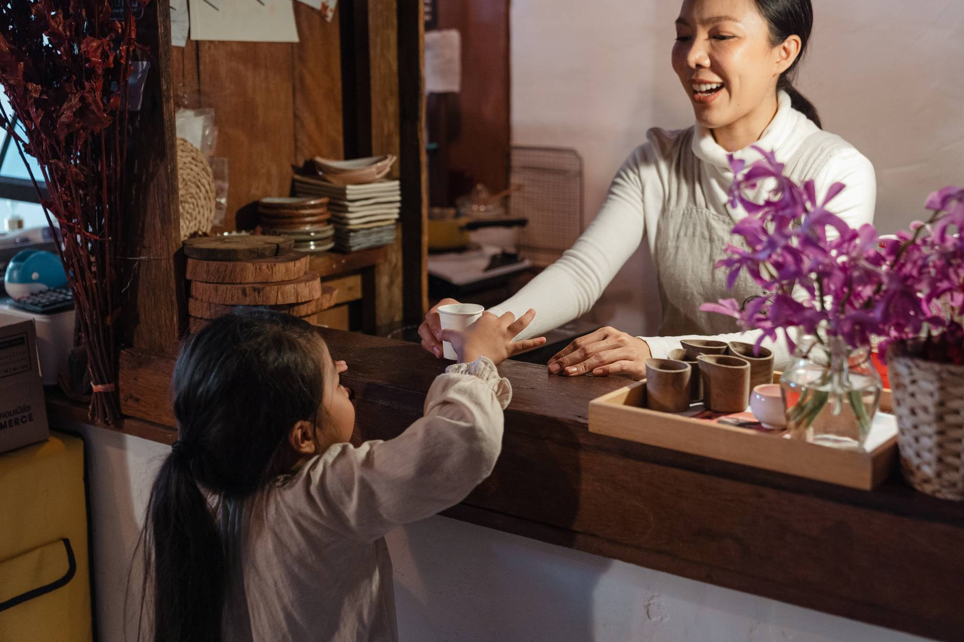 crop ethnic mother serving little girl glass of refreshing drink