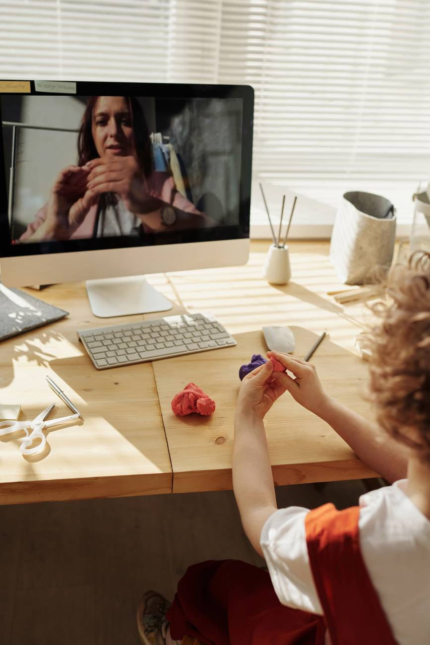 photo of kid playing with kinetic sand while watching through imac